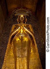 Golden standing buddha in a pagoda Bagan