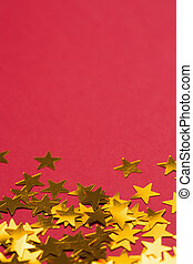 Golden star decorations spread out on red background