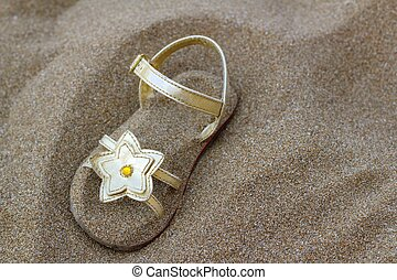 golden star sandal buried in summer beach sand vacation metaphor