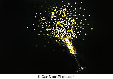 Golden star shaped confetti and party streamers poured out of champagne glass on black background. Flat lay style. Celebration concept.