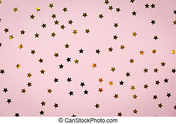 Golden star sprinkles on pink. Festive holiday background....