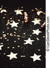 Golden stylish stars and confetti decoration on black background.