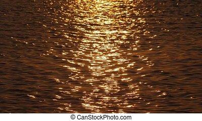 Golden sun path on dark sea water - Slow motion shot of...