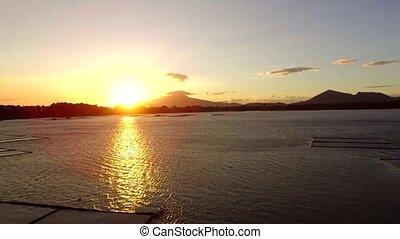 Golden sun setting over aqua fish farming bamboo structures...