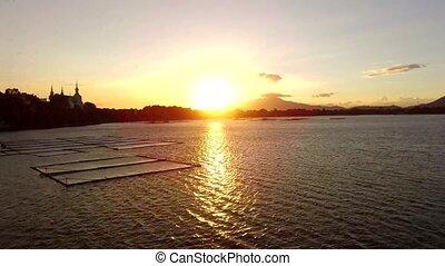 Golden sun setting over aqua fish farming bamboo structures on mountain lake. Drone aerial shot