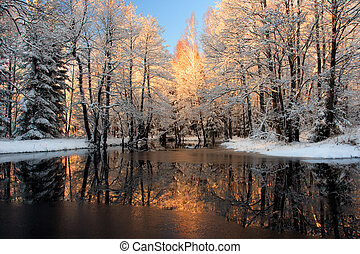 Brilliantly golden sunlight reflecting in river in Wintry.