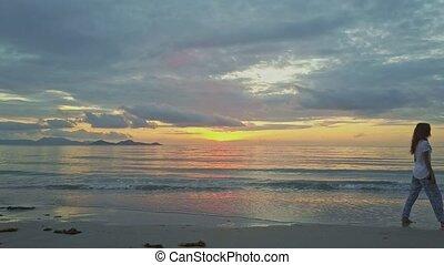 Golden Sunrise above Ocean Girl Passes Camera on Beach