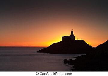 Golden sunrise over Mumbles lighthouse