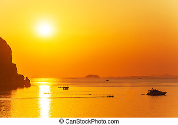 Golden sunset background with boats. Phi Phi islands, Thailand.
