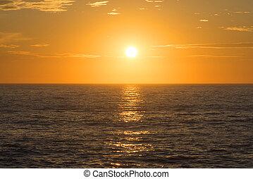 Golden sunset centered over empty ocean