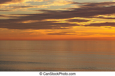 Golden sunset colors of orange, gold, blue clouds reflected in calm ocean