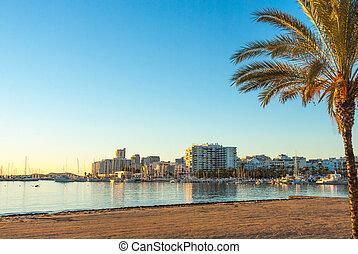Golden sunset on beach & marina in St Antoni de Portmany, Ibiza, Spain.