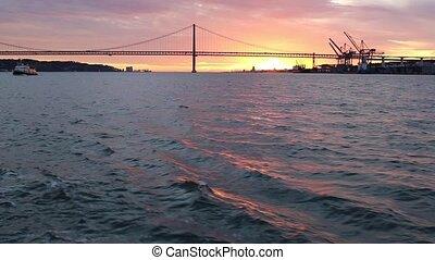 Golden sunset on the background of 25th April Bridge Lisbon