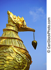 golden swan statue and blue sky