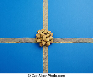 golden textile ribbon crossed on a blue background, in the middle a knotted bow