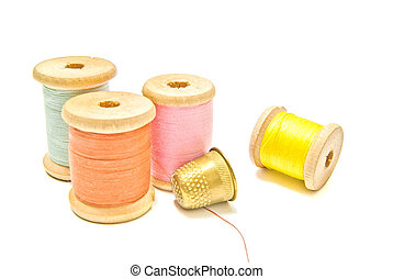 golden thimble and spools of thread