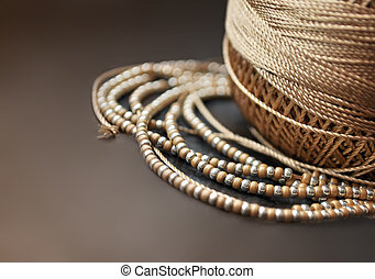 Golden threads and beads on dark background