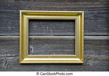 golden vintage empty frame on old wooden wall