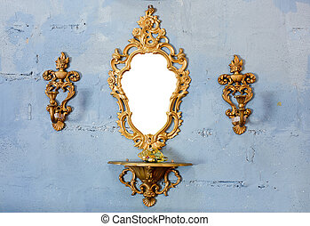 Golden vintage mirror with gold candlestick on wall