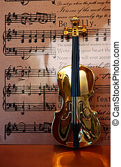 Golden violin standing in front of musical notes and text background.