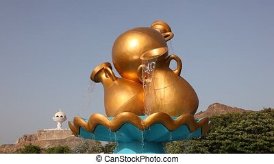 Golden water jug, Oman - Golden water jug at a roundabout in...