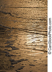 Golden waves texture on the beach
