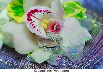Golden wedding rings lie inside lily flower in the bouquet. on window sill. Bride's traditional symbolic accessory. Symbol of love and marriage.