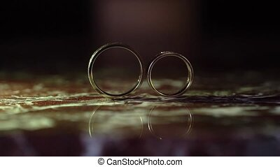 Golden wedding rings on marble rolls out of the frame movement.