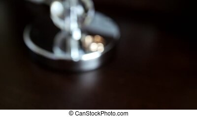 Golden wedding rings on metal surface in rack focus, close...