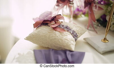 golden wedding rings on small white cushion.
