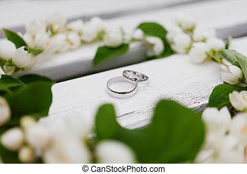 Golden wedding rings with diamonds lie inside jasmine...