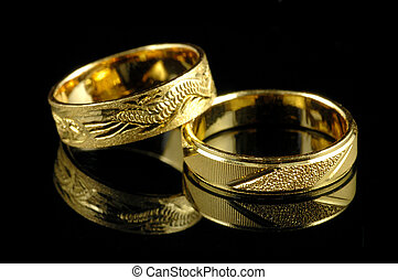 Golden wedding rings with reflection in isolated black ...