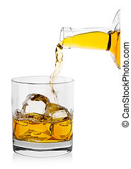 Golden whiskey pours from  bottle into glass with ice