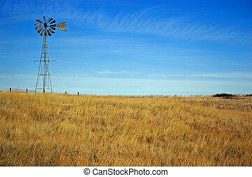 Golden Windmill - A windmill overlooks a golden field of ...