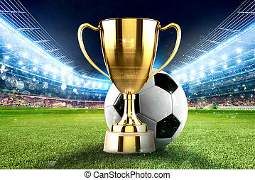 Golden winner s cup in the middle of a soccer stadium with...