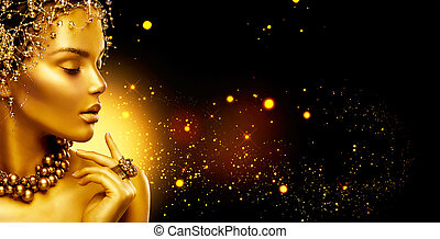 Golden woman. Beauty fashion model girl with golden make up, hair and jewellery on black background
