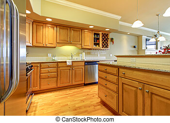 Golden wood kitchen with granite and stainless steal.