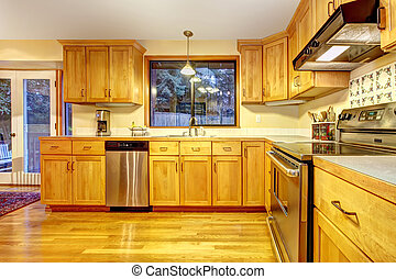 Golden wood kitchen with hardwood floor.