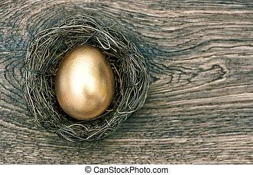goldenes, osterei, in, nest, auf, hölzern, hintergrund