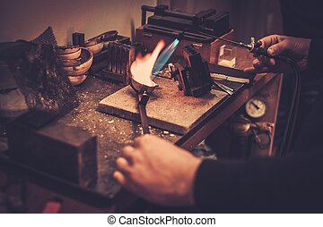 Goldsmith melting gold to liquid state in crucible with...