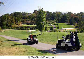A lovely golf course in Branson Missouri USA with carts in foreground and golfers on green in background.