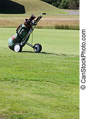 Golf bag and cart on green