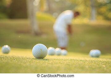 Golf ball and blurred of man playing golf in green course -...