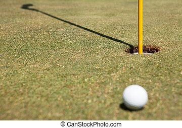 Golf ball and flag in hole