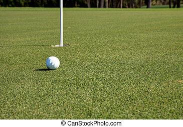 Golf ball and flag on Lush green grass