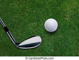 Golf ball and golf putter on green grass land .