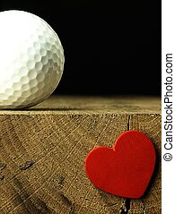 Golf ball and heart on the edge of table