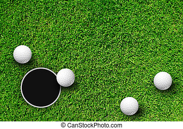 Golf ball and hole - Golf ball on putting green next to hole