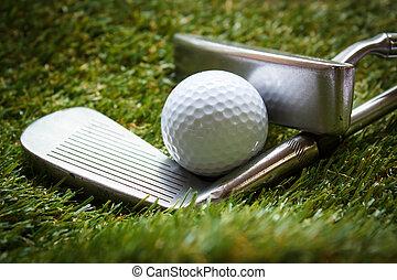 Golf ball and putter. - Golf ball and putter on green grass...