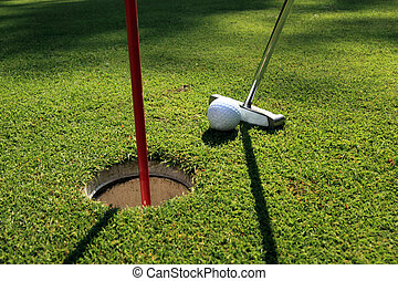 Golf ball and putter on a green